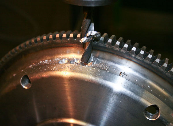 Removing weight from the flywheel to reduce unbalance